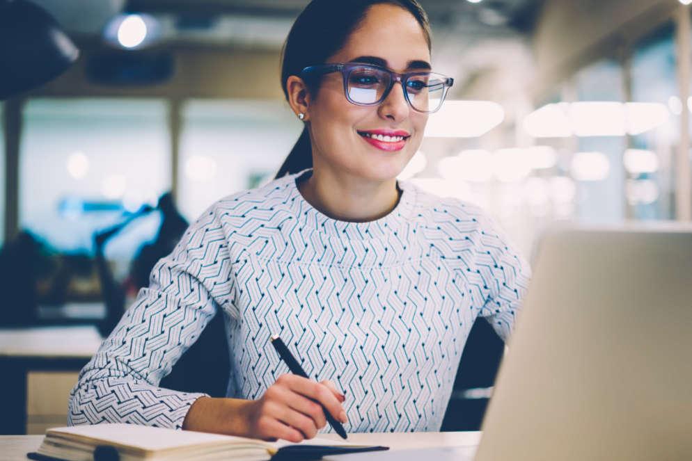 Online Steuerberaterkurse Symbolbild eine Frau schaut auf einen Laptop und schreibt in ein Buch